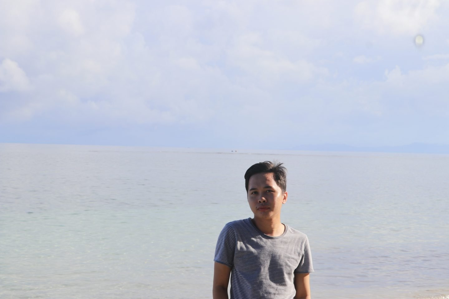 Photo of Sam Dapanas in front of ocean and blue sky